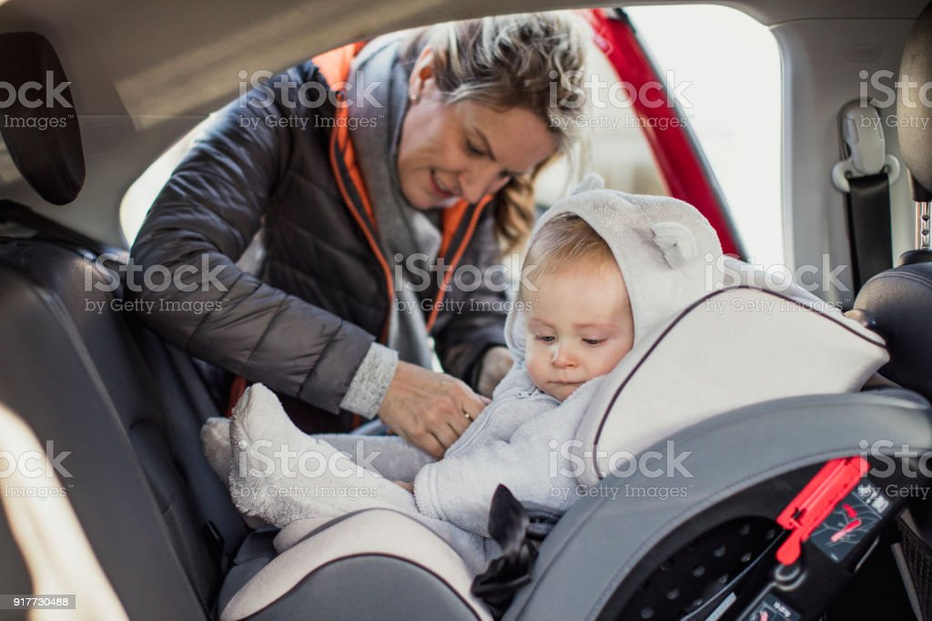 Putting Him in His Car Seat stock photo