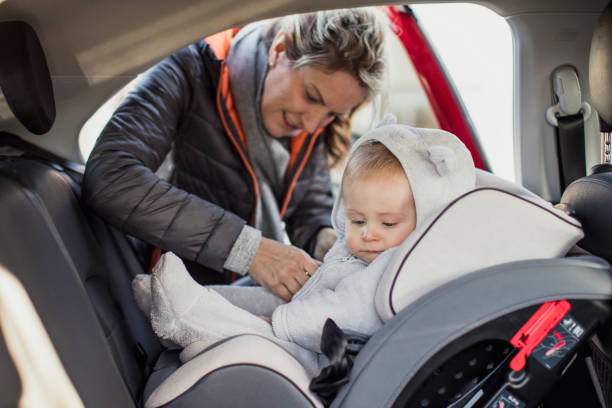 putting him in his car seat - day in the life series stock pictures, royalty-free photos & images