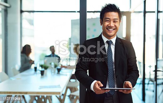 Cropped shot of a handsome young businessman using a tablet in the workplace