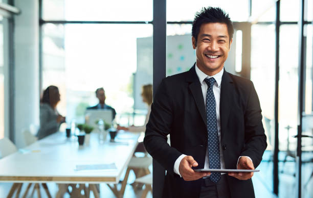 Putting his business online Cropped shot of a handsome young businessman using a tablet in the workplace japanese ethnicity stock pictures, royalty-free photos & images
