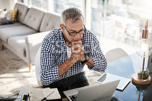 High angle shot of a mature man working on a laptop at home
