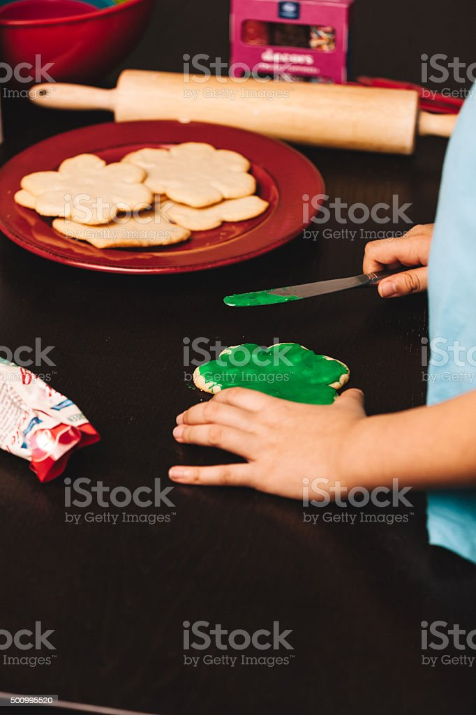 putting icing on cookies stock photo
