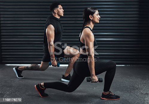 Shot of two sporty young people exercising together against a dark background