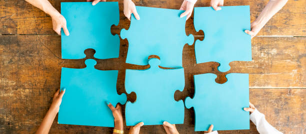 Putting it all together! Team of doctors and nurses and business people work together to make the pieces fit. jigsaw piece stock pictures, royalty-free photos & images