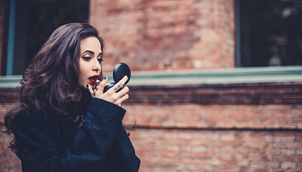 putting lippenstift auf  - winterjacke lang damen stock-fotos und bilder
