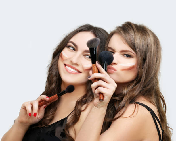 putting make-up. frau mit einem pinsel für make-up. freundinnen setzen make-up - gesicht make up anleitungen stock-fotos und bilder