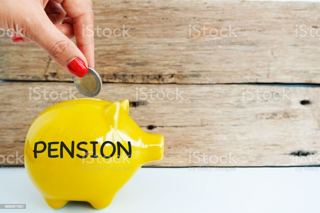 Putting money in a yellow piggy bank for pension, social security concept stock photo