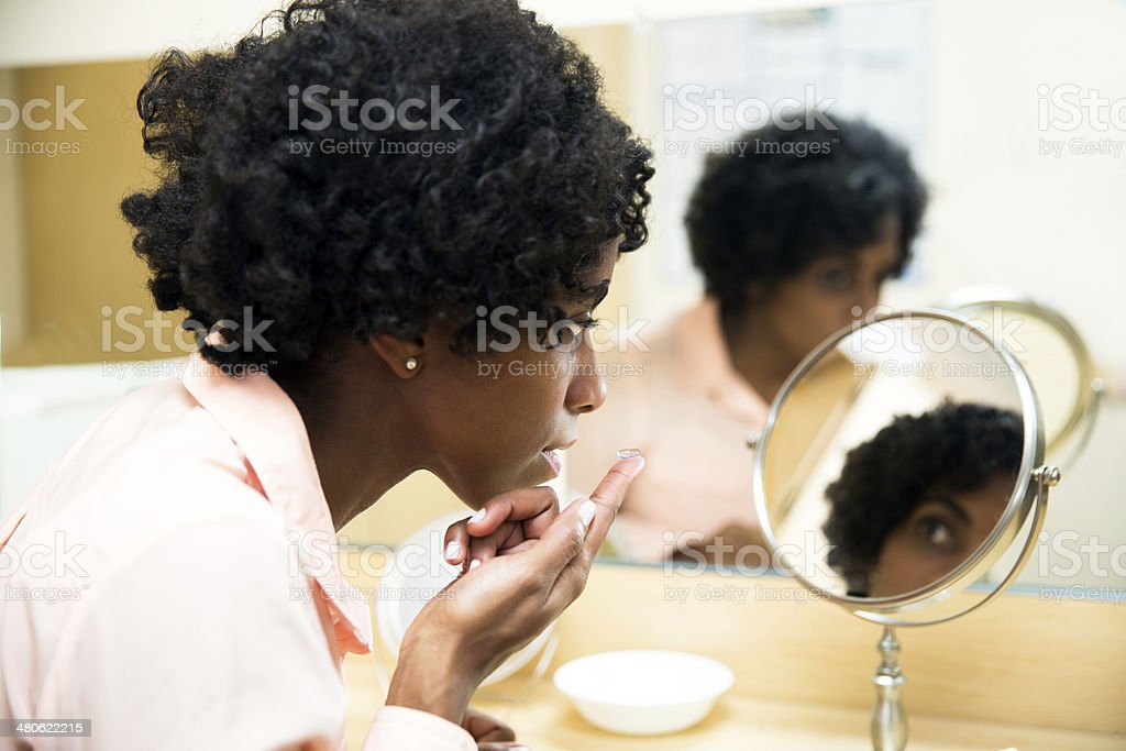 Putting on a corrective contact lens at the optometrist's office stock photo