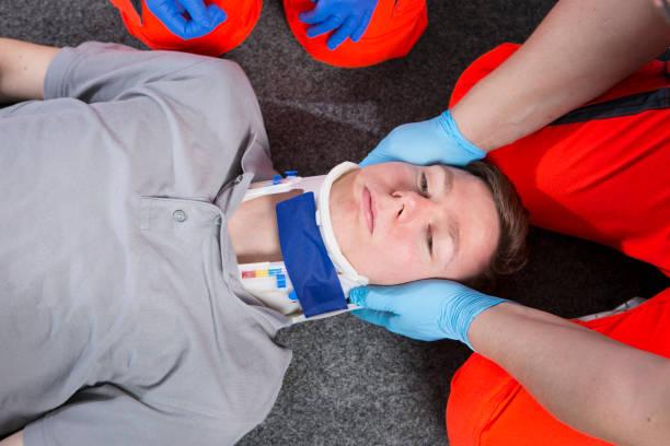 Putting on a neck brace, cervical collar - putting on the neck brace stock photo