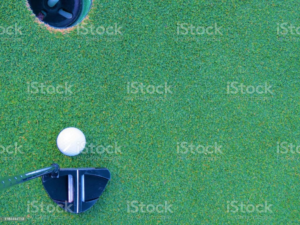 putting on golf green, ball in flag hole