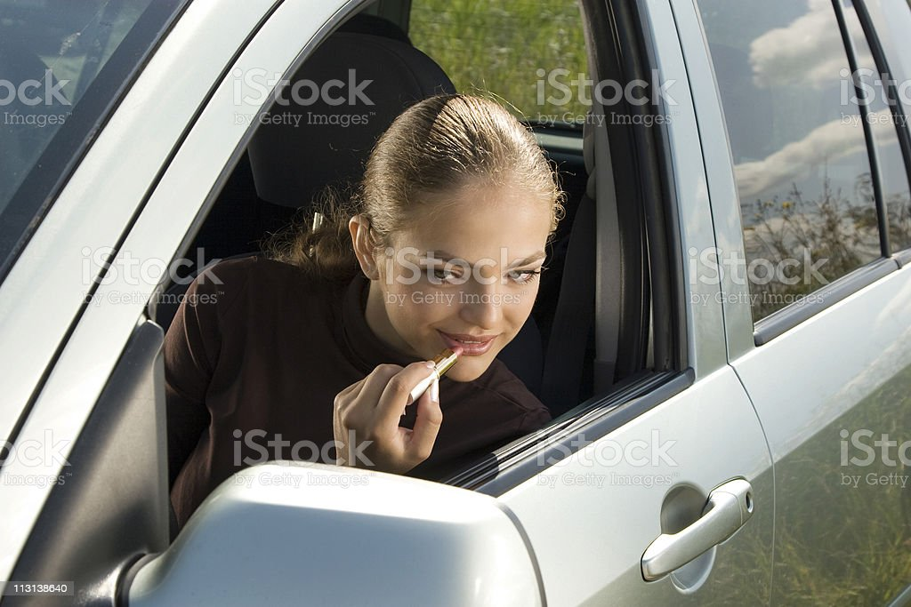 Putting on lipstick in the car royalty-free stock photo