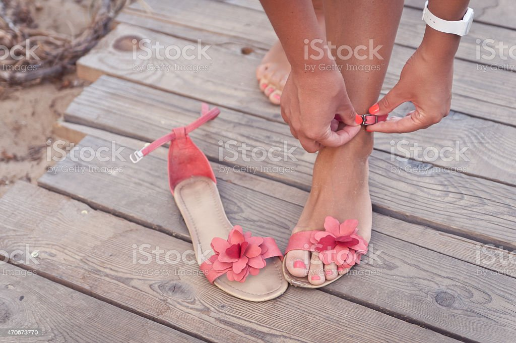 Putting on sandals at the beach stock photo