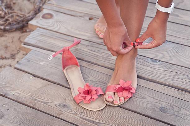 putting auf sandalen am strand - salzwasser sandalen stock-fotos und bilder