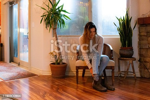 Woman putting on shoes at home on a rainy day