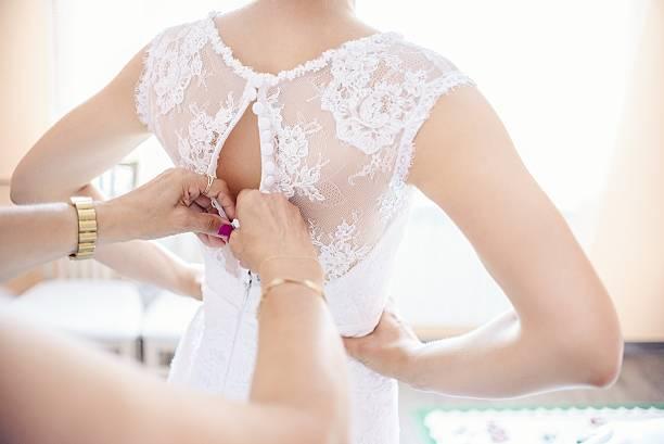 Putting on wedding dress stock photo