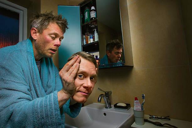 putting on your morning face - mirror mask stockfoto's en -beelden
