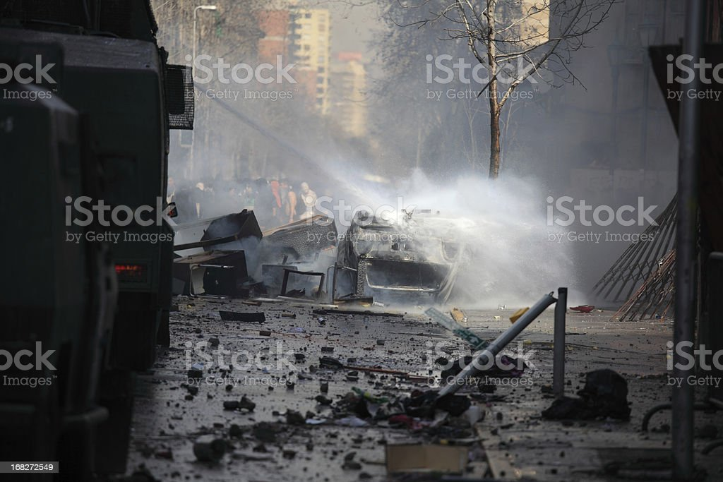 Putting out a burning car with water in a wrecked street stock photo