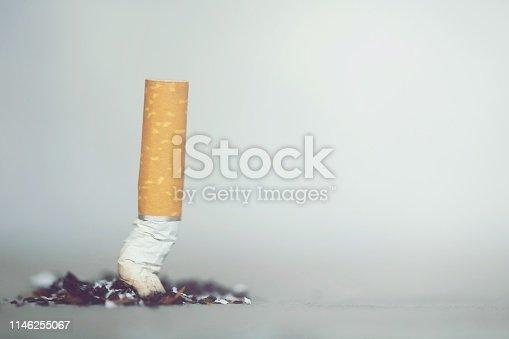 putting out a smoking a cigarette., cigarette butt on Concrete floor, bare cement.