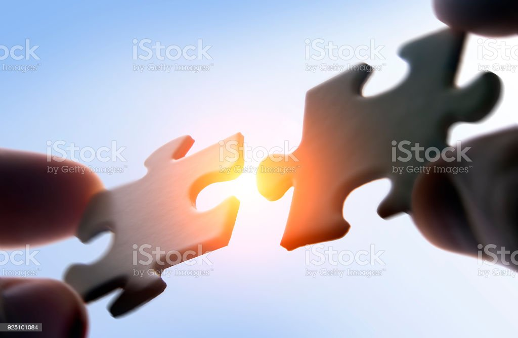 Putting puzzle pieces together stock photo