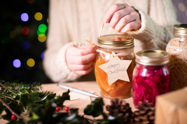 Putting Reusable Wooden Gift Tag On Homemade Jars Of Preserved Fruit For Eco Friendly Christmas Gift Putting Reusable Wooden Gift Tag On Homemade Jars Of Preserved Fruit For Eco Friendly Christmas Gift homemade stock pictures, royalty-free photos & images