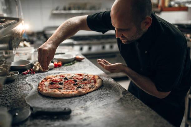 Putting seasoning on pizza stock photo