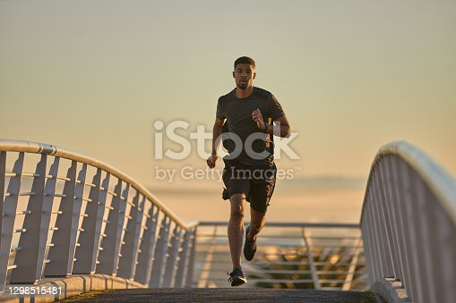 Shot of a sporty young man running on a bridge in the city