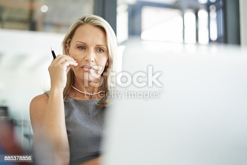 Shot of a mature businesswoman using a laptop in a modern office and looking thoughtful