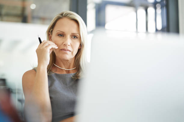 Putting some serious mind work into a work task Shot of a mature businesswoman using a laptop in a modern office and looking thoughtful ambiguity stock pictures, royalty-free photos & images