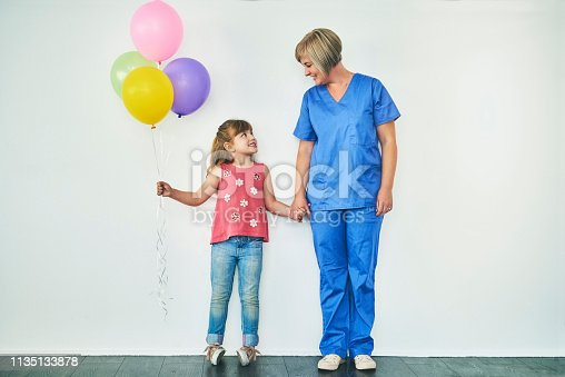 Studio shot of an adorable little girl holding a bunch of balloons and holding her doctor's hand