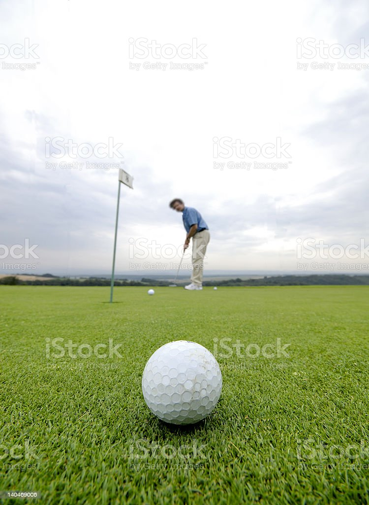 Man putting the ball at the golf course. Ball at foreground very...
