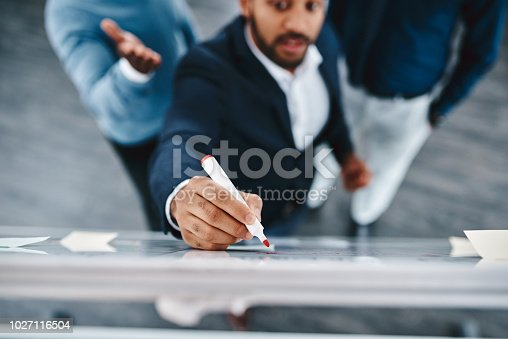 High angle shot of three businessmen brainstorming together on a whiteboard in an office