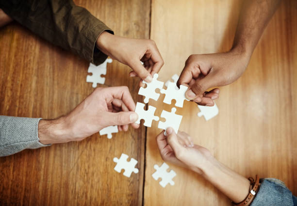 Putting the pieces together High angle shot of a group of unrecognizable university students building a puzzle while studying in the library jigsaw piece stock pictures, royalty-free photos & images