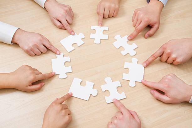 mettere il puzzle nel lavoro di squadra - mano donna dita unite foto e immagini stock