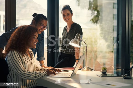 Shot of a group of young businesspeople using a laptop during a late night at work