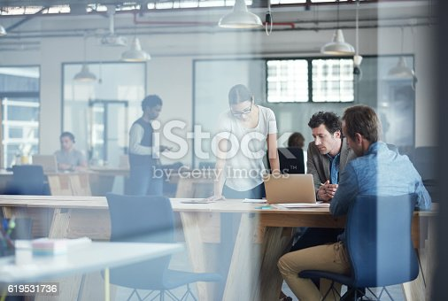 Shot of a group of colleagues talking together over a laptop in an office