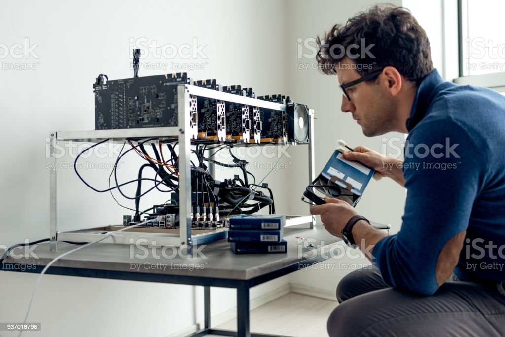 Putting together crypto currency machine - Royalty-free Adult Stock Photo