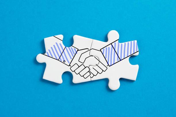 Putting Together Handshake Jigsaw Puzzle stock photo