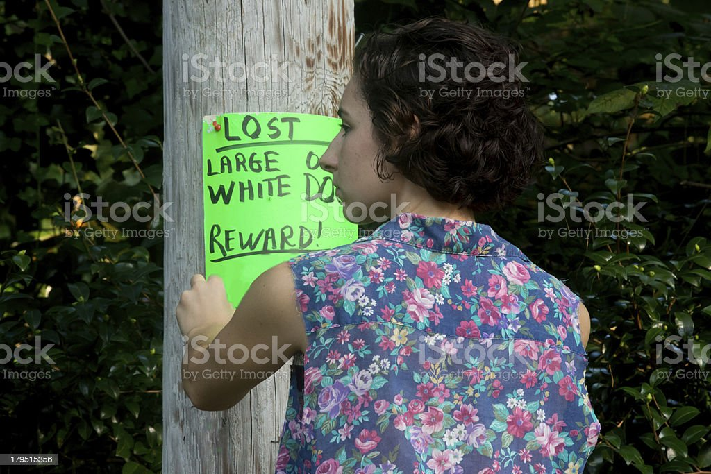 young woman putting up lost dog posters