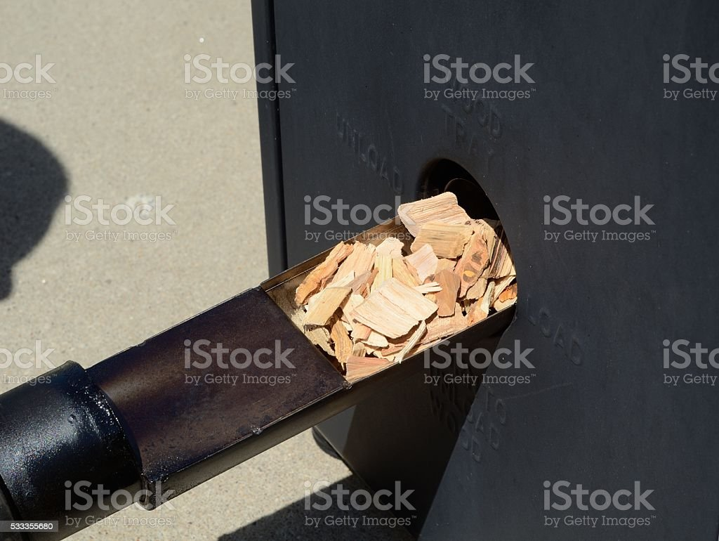 Putting Wood Chips in a Smoker stock photo