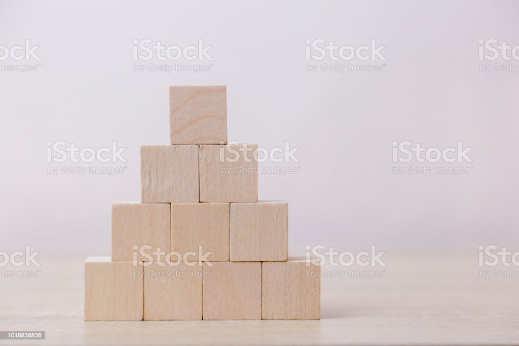 Putting wood cube block on top pyramid,With the concept of a thriving...