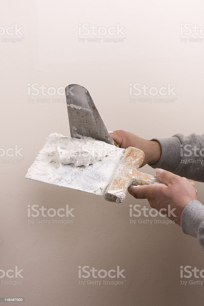 Putty Knife with Paste to Repair Wall Damage stock photo
