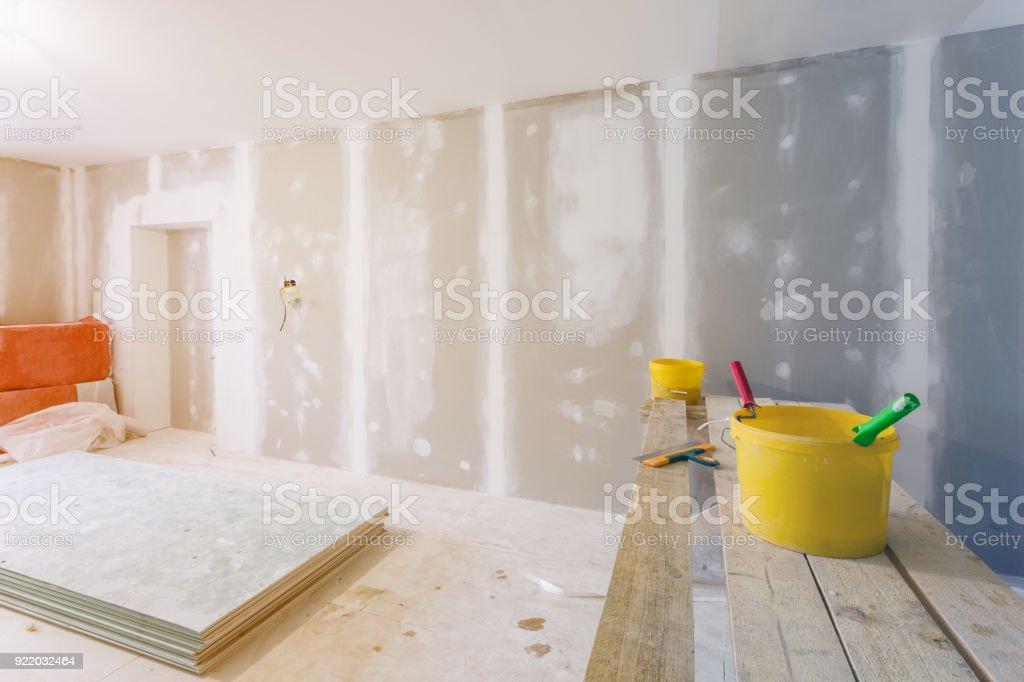 Spachtel, gelber Eimer mit Leim und Leimwalzen auf dem Holzbrett in Raum ist unter Bau, Umbau, Renovierung, Ausbau, Restaurierung und Umbau. – Foto