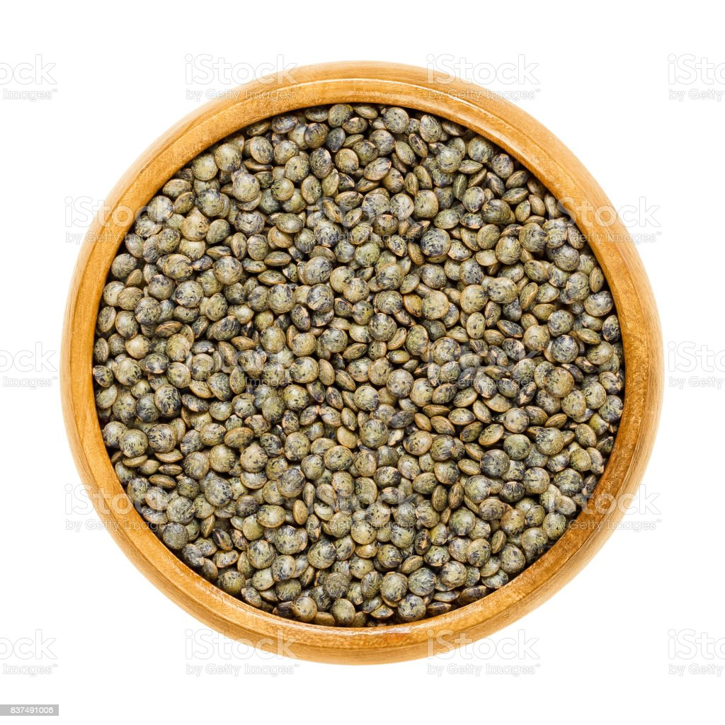 Puy lentils in wooden bowl over white stock photo