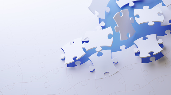 White jigsaw puzzle pieces on blue background. Horizontal composition with copy space. Great use for puzzle concepts.