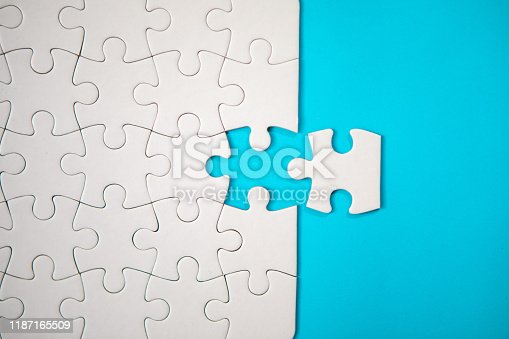 istock Puzzle Concept - White Jigsaw Puzzle Pieces On Blue Background 1187165509
