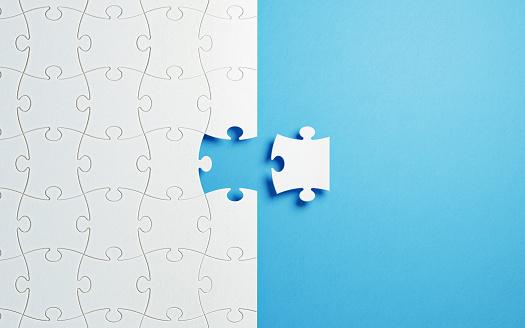Puzzle Concept - White Jigsaw Puzzle Pieces On Blue Background