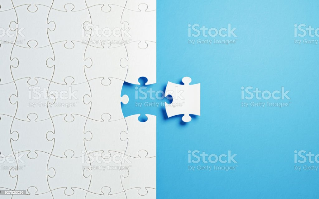 Puzzle Concept - White Jigsaw Puzzle Pieces On Blue Background stock photo