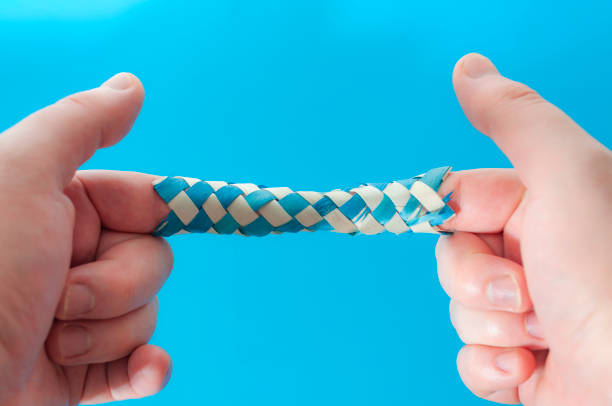 puzzle game and logic games concept with hands playing with a chinese finger trap, a toy that the more you pull the tighter it gets stuck and you need to push to escape isolated on blue background - trappola foto e immagini stock