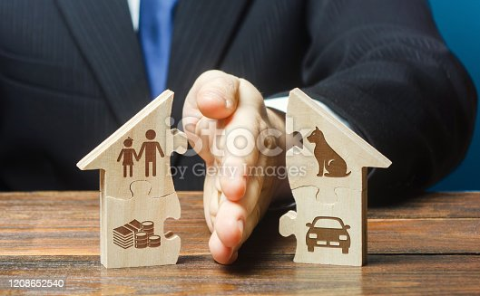 istock Puzzle house is divided into two equal parts by a lawyer in a divorce process. Protection of rights. Conflict resolution. Court, justice. Disputes over fair division of marital property real estate. 1208652540