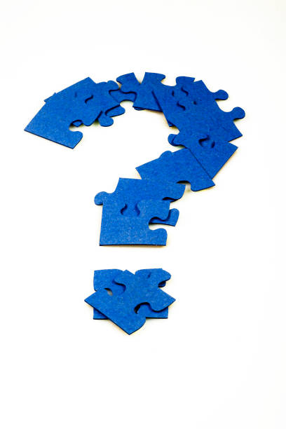 Puzzle in the shape of a question mark on a white isolated background stock photo